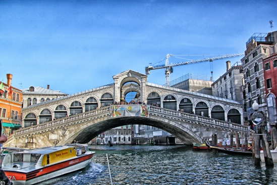 The Rialto Bridge (Italian: Ponte di Rialto) is one of the four bridges spanning the Grand Canal in Venice, Italy. It is the oldest bridge across the canal, and was the dividing line for the districts of San Marco and San Polo.